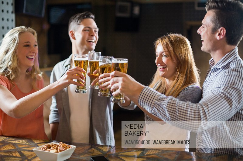 Smiling friends toasting glasses of beer at counter in bar