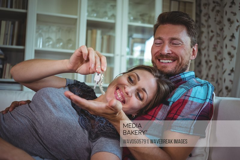 Happy couple holding their house key at home