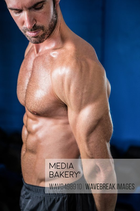 Shirtless athlete looking at biceps while standing in gym