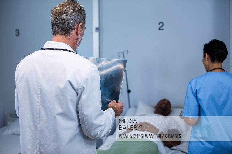 Doctor analyzing x-ray while nurse interacting with patient during visit in ward