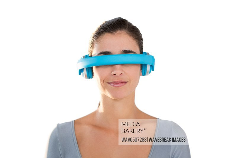 Smiling woman in exercise outfit using virtual video glasses against white background