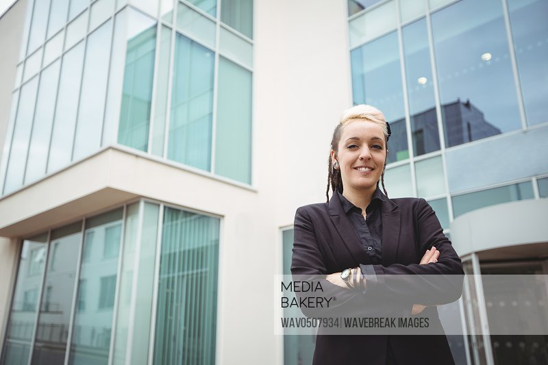 Portrait of smiling businesswoman standing with arms crossed in office campus