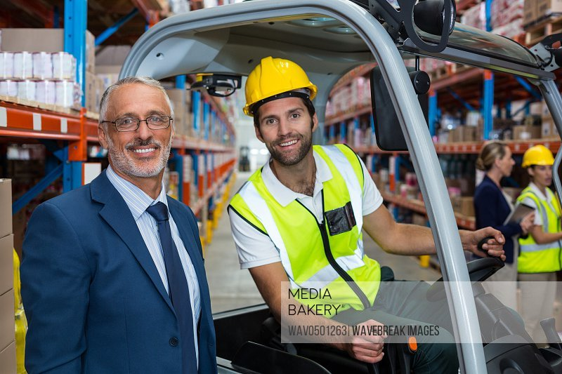 Warehouse worker and his manager smiling at camera in a warehouse