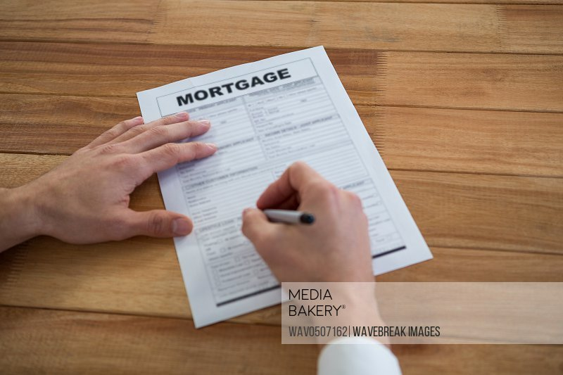 Businessman filling mortgage contract form in office