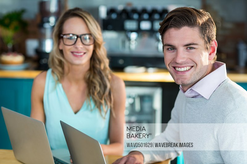 Portrait of smiling man and woman using laptop during meeting in cafe