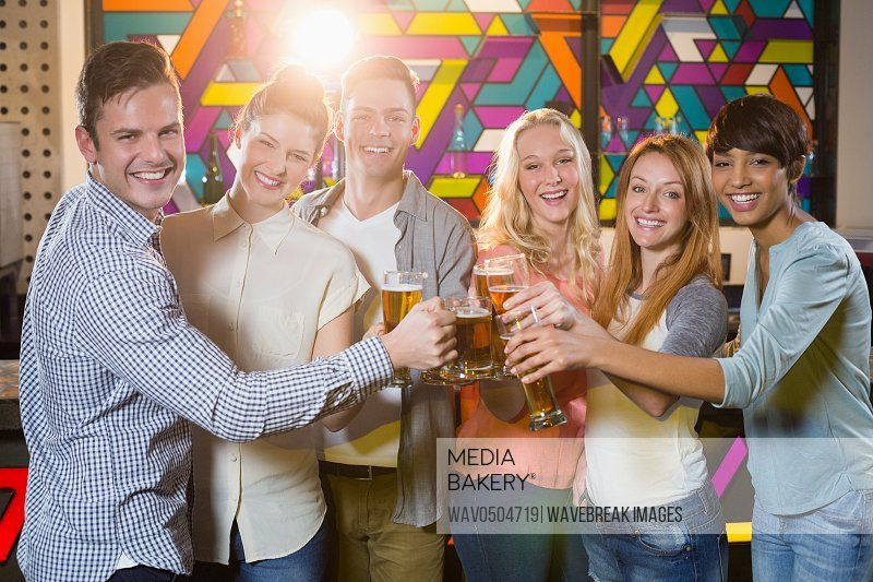 Portrait of smiling friends toasting glass of beer in bar