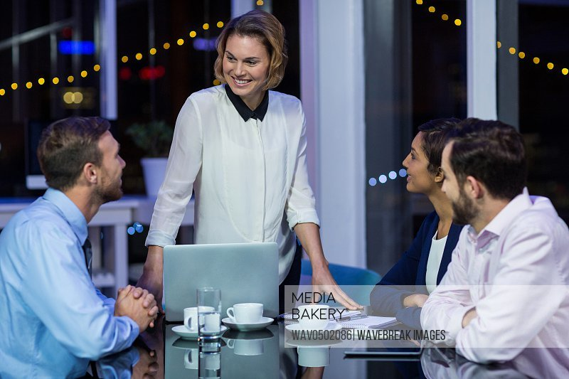 Businesswoman interacting with her colleagues in office at night