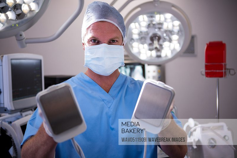 Portrait of male surgeon holding defibrillator at the hospital
