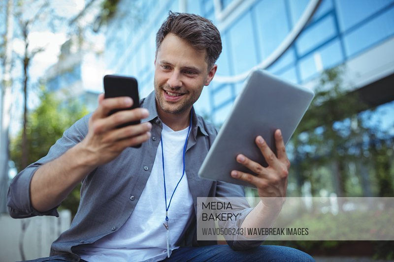 Business executive using mobile phone and digital tablet outside office