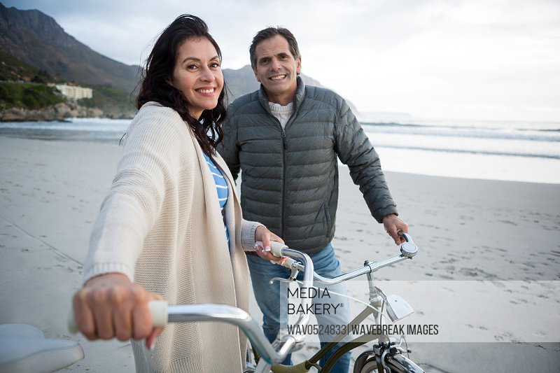 Portrait of couple standing with bicycle on beach