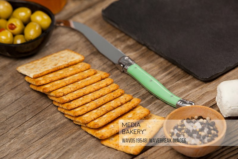 Bowl of green olives biscuit and knife on wooden table