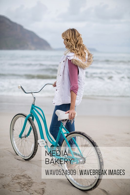 Mature woman standing with bicycle on the beach