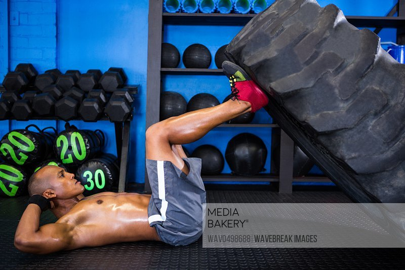 Side view of male athlete with tire while exercising in gym