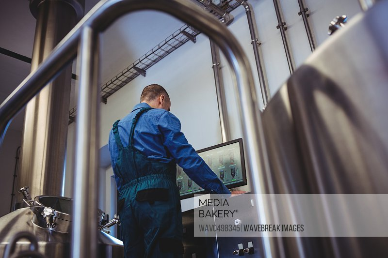 Low angle view of male manufacturer using computer at brewery