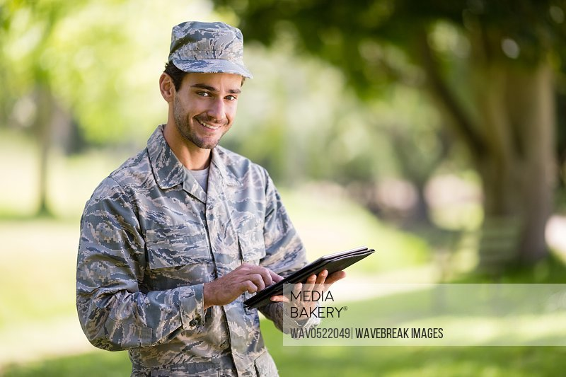 Soldier using digital tablet in park