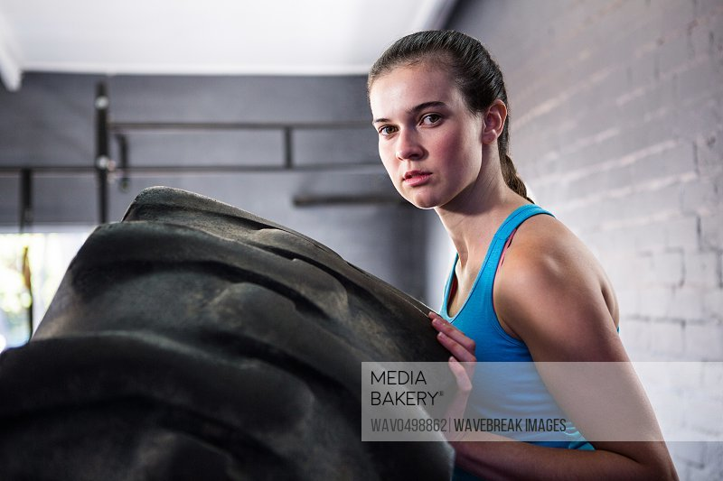 Portrait of female athlete pushing tire while exercising in gym