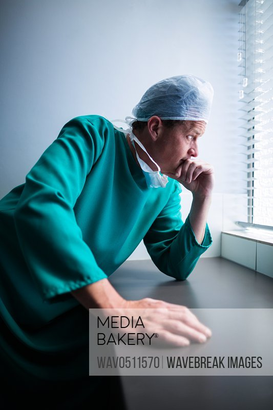 Thoughtful male surgeon looking through window in hospital
