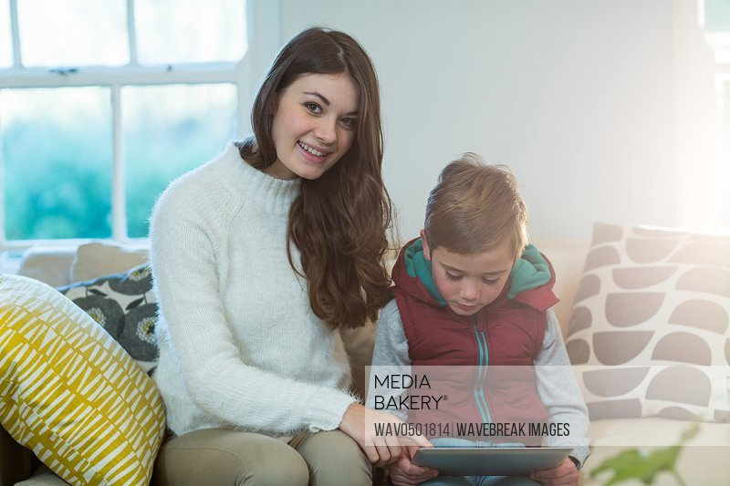 Mother and son using digital tablet at home