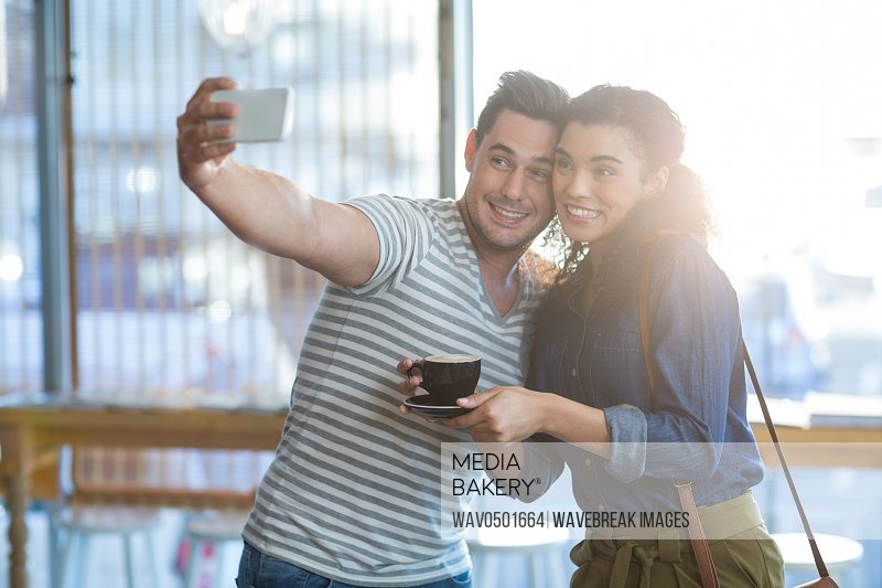 Smiling young couple taking selfie while having coffee in cafA?