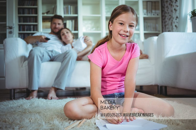 Girl sitting on the floor and drawing while parents sitting on sofa