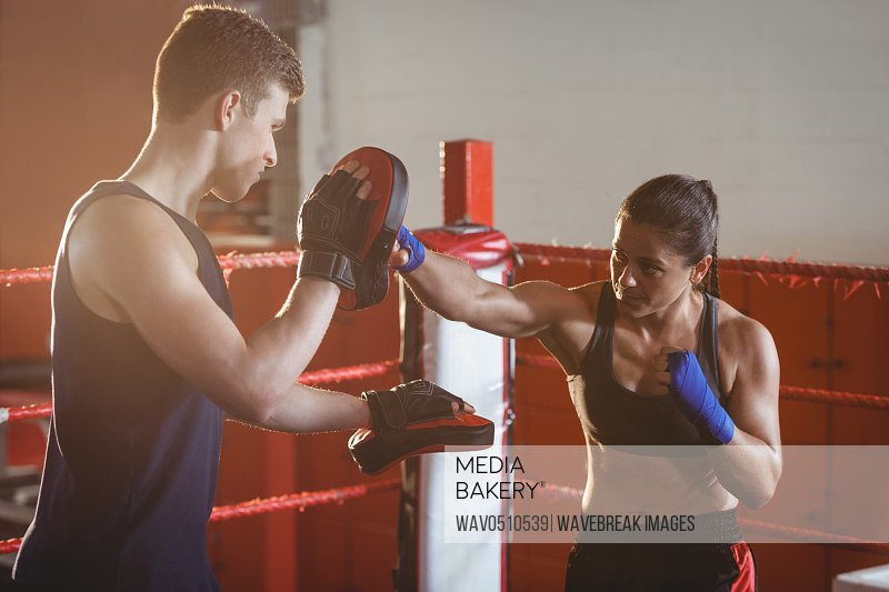 Female boxer practicing with trainer in the ring at fitness studio
