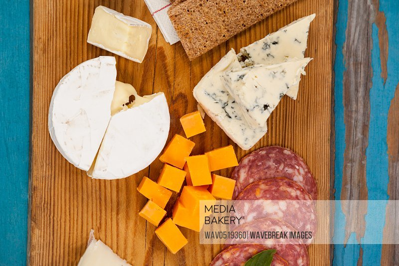 Cheese with ham and crispy biscuits on chopping board