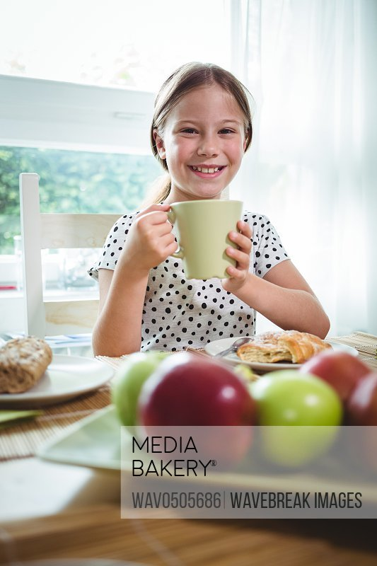 Smiling girl having coffee at breakfast table