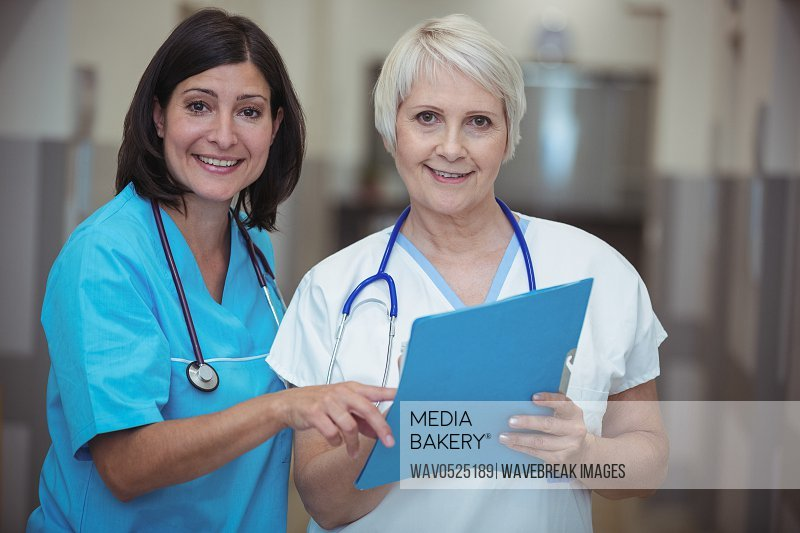 Portrait of female surgeon and nurse having discussion on file