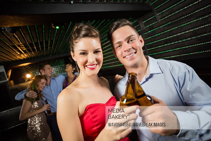 Portrait of happy couple toasting a beer bottles in bar