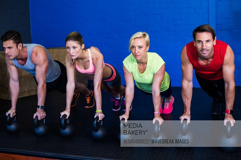 Young male and female athletes exercising with kettlebells in fitness studio