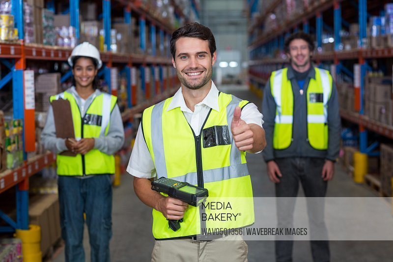 Warehouse worker showing thumbs up sign in warehouse