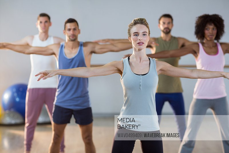 Group of people performing exercise in gym