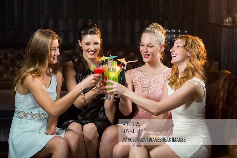 Smiling female friends toasting glasses of cocktail in bar