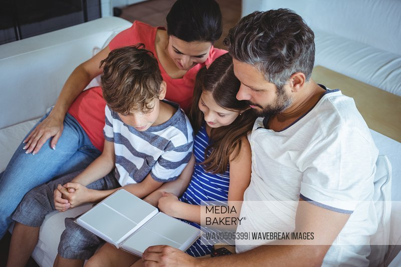 Family sitting on sofa and looking at a photo album at home