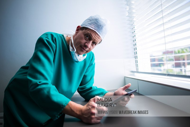 Portrait of male surgeon using digital tablet at window of hospital