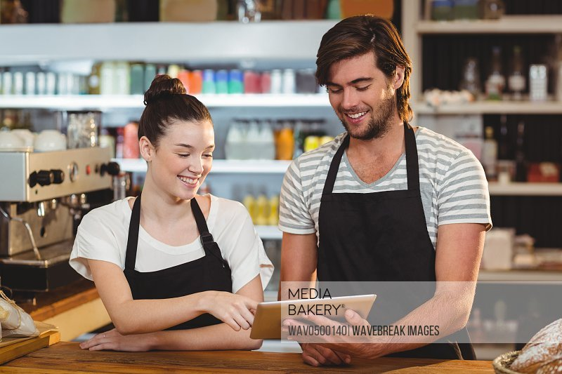 Smiling waiter and waitress using digital tablet at counter in cafe