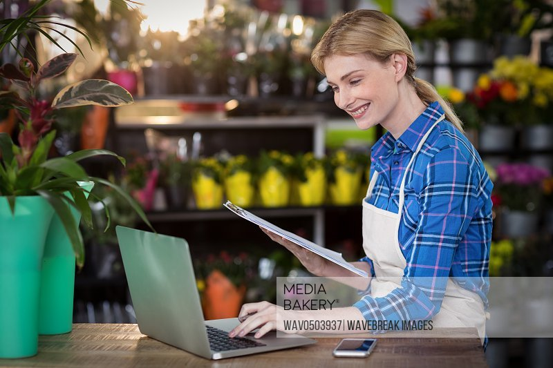 Female florist using laptop while holding clipboard in the flower shop
