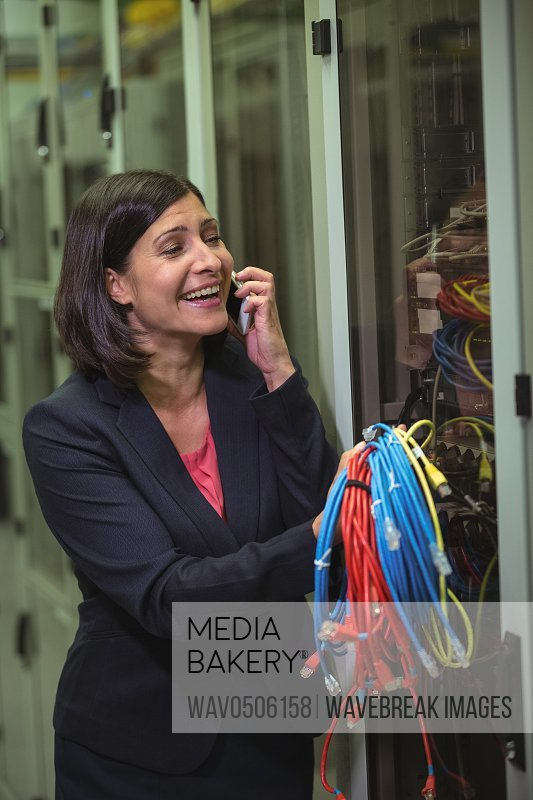 Technician holding patch cable while talking on mobile phone in server room