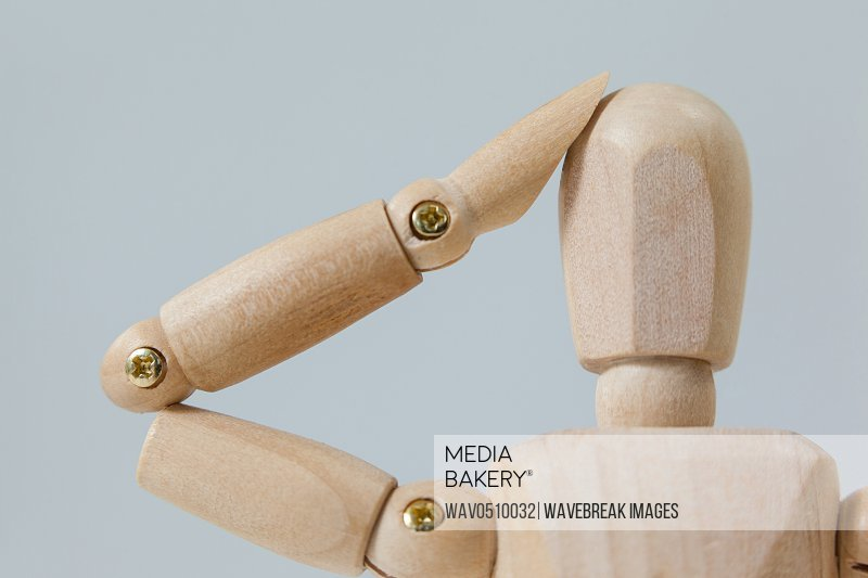 Confused wooden figurine with hand on head against white background