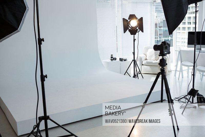 Photo studio with tripod lighting equipment and digital camera