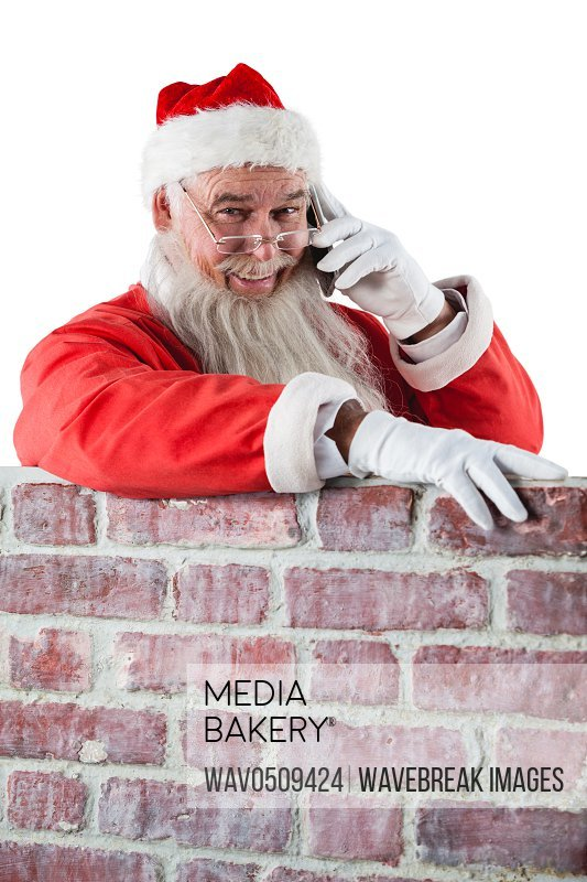 Santa claus standing beside chimney and talking on mobile phone