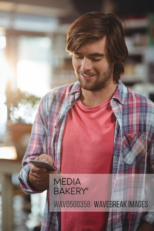 Smiling man using mobile phone in cafe