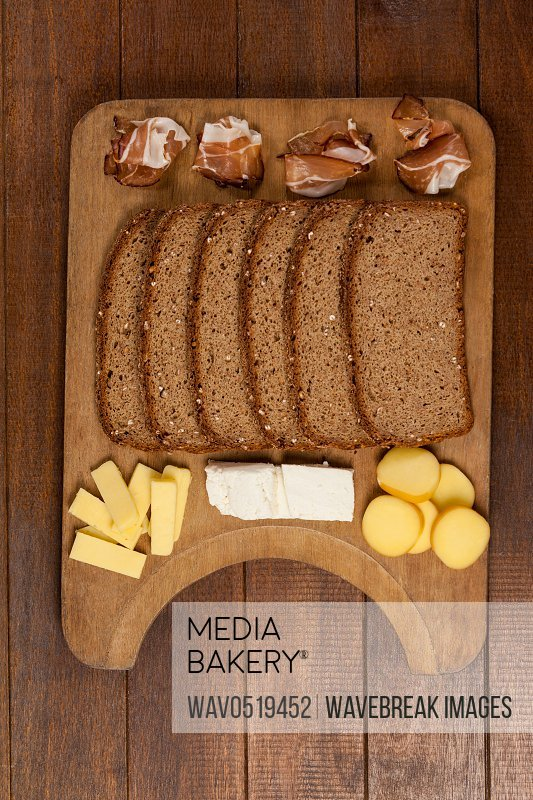 Slices of brown bread meat and cheese on wooden chopping board