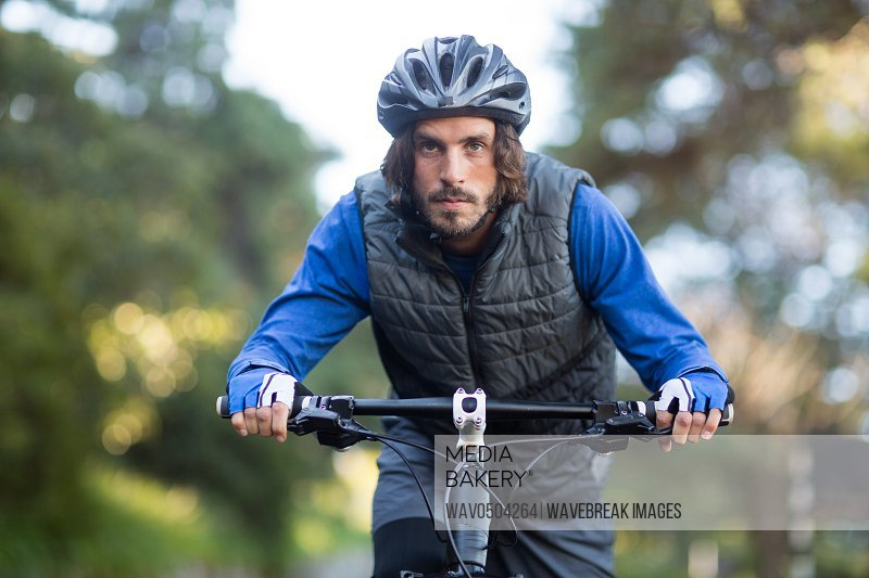 Male biker cycling in countryside on sunny day