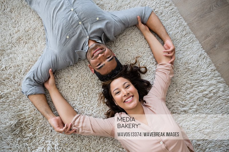 Portrait of happy couple lying on rug in living room