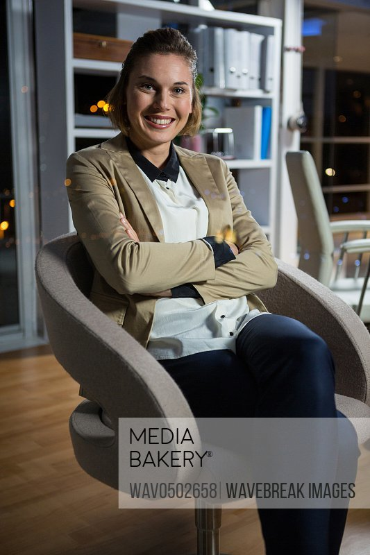 Portrait of businesswoman sitting on chair in office at night