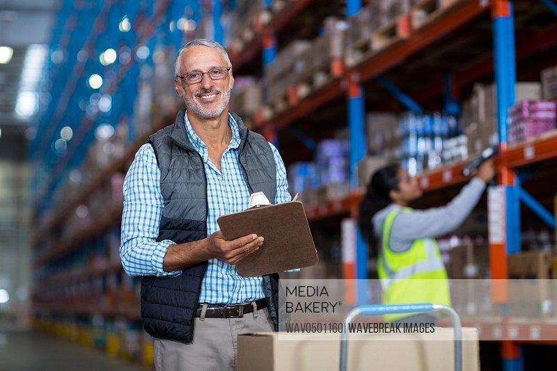 Warehouse manager smiling and holding clipboard in warehouse