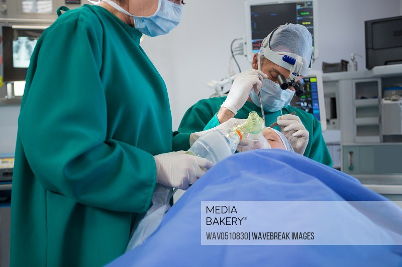 Surgeon operating patient in operation theater of hospital