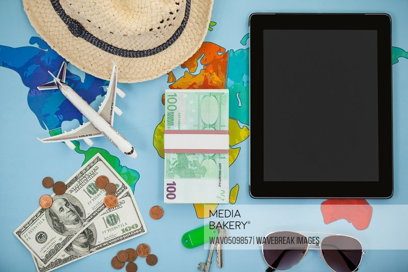 Digital tablet, hat, sunglasses, dollar and airplane model on map