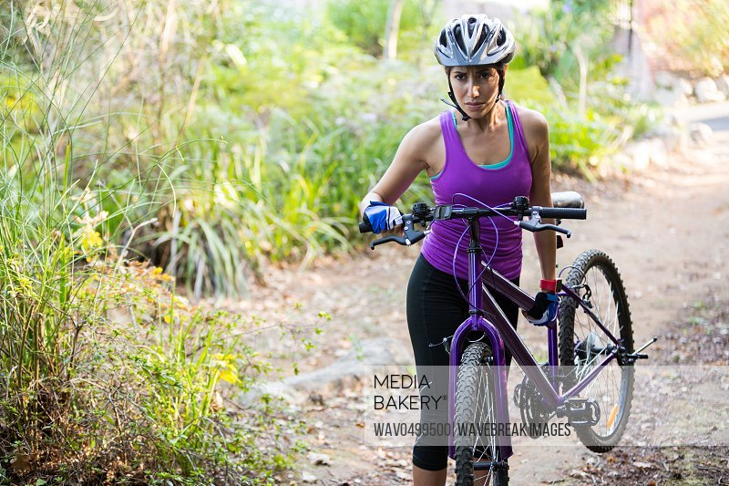 Female cyclist carrying mountain bike while walking in park